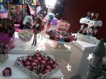 Mesa decorada com tema monster high com doces personalizados.