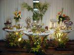 Mesa de café, outra de petit-four e outra de doces. Decoração c/ arranjos tropicais de flores e plantas naturais.Doc.3-CF