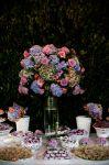 Mesa de doces finos, acompanha decoração de flores liláses.Doc.3-BO