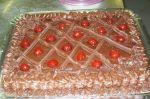 bolo com massa de chocolate recheio prestigio e cobertura toda de chocolate com decoração de cerejas
