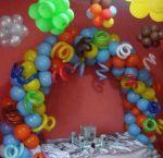 Arco espiral com cobrinhas,bexigas no teto e mesa de doce.