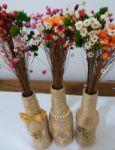 Centro de mesa Garrafas decoradas com sisal e juta. Iniciais ou fita/fio com contas/caracol e meias pérolas. Mini ramalhete de florzinhas coloridas a parte.